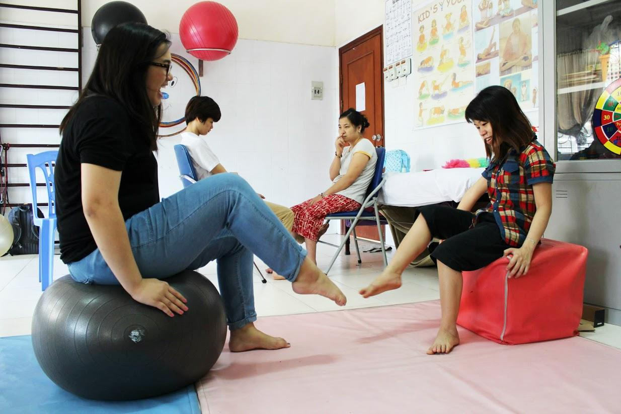 A child does physical exercises with a student doing an Occupational Therapy internship abroad in Vietnam.